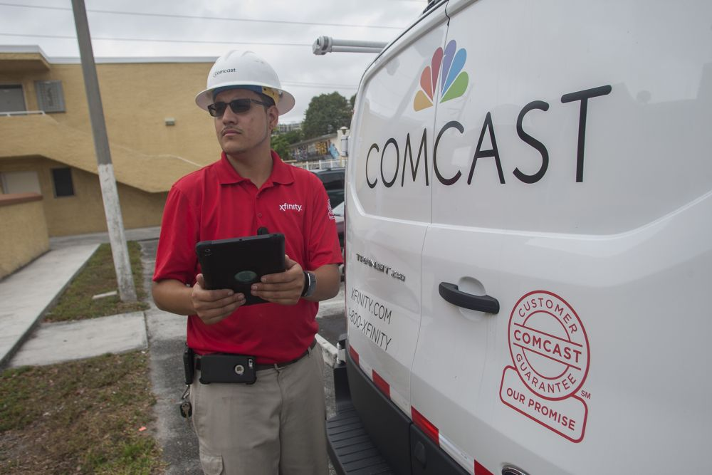 Comcast technician in front of fleet vehicle
